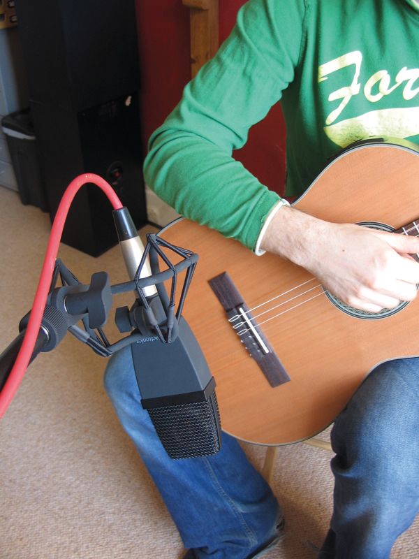 As a starting point that is favoured by many engineers, position the microphone at the place where the guitar's neck joins the body. Experiment with distance to achieve a good balance of direct sound and room ambience, and also try some less obvious positions such as placing the mic at the player's shoulder level.