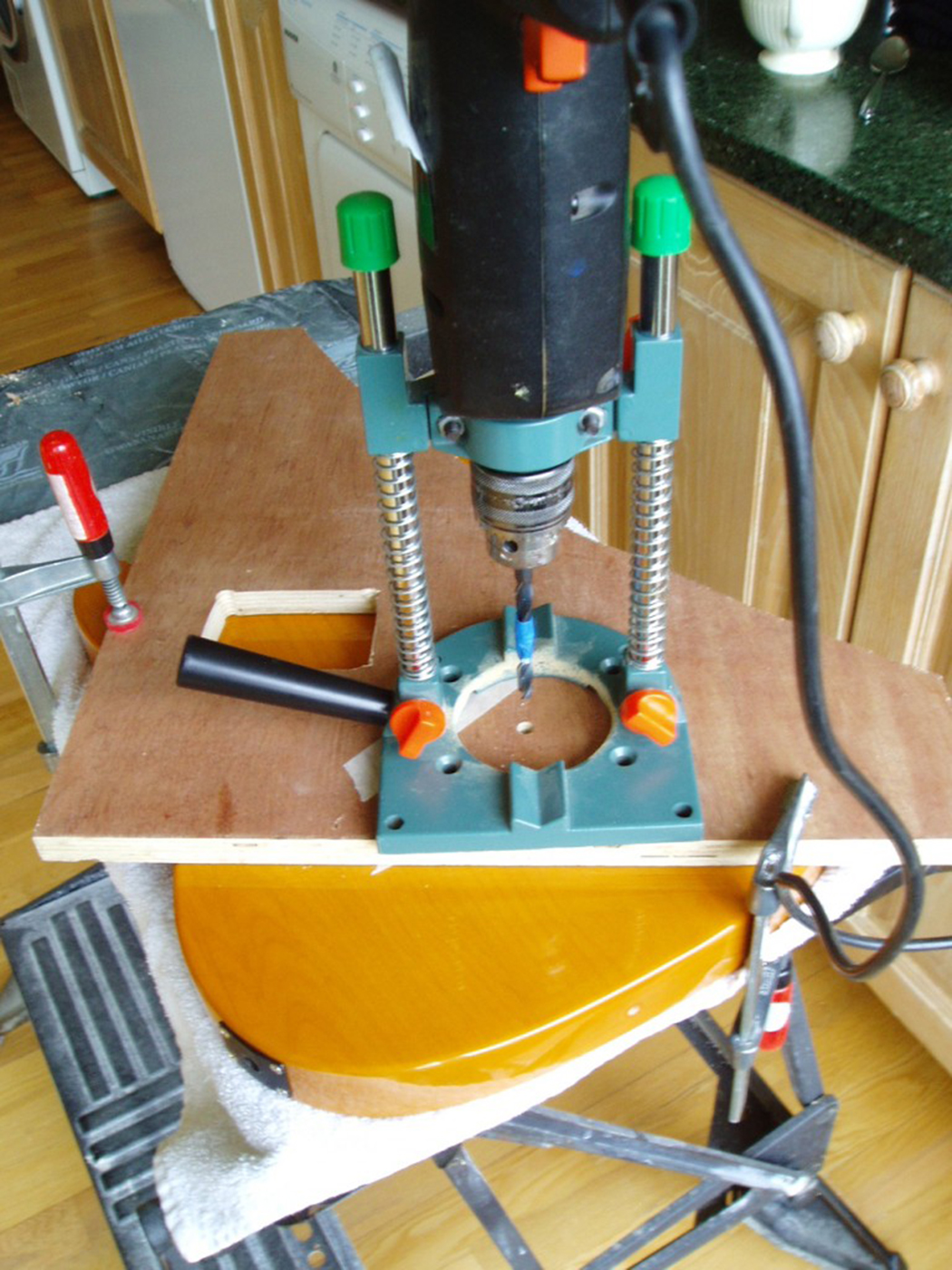 the plywood is clamped in position with our drill mounted in a special  drill guide that positions the drill dead square