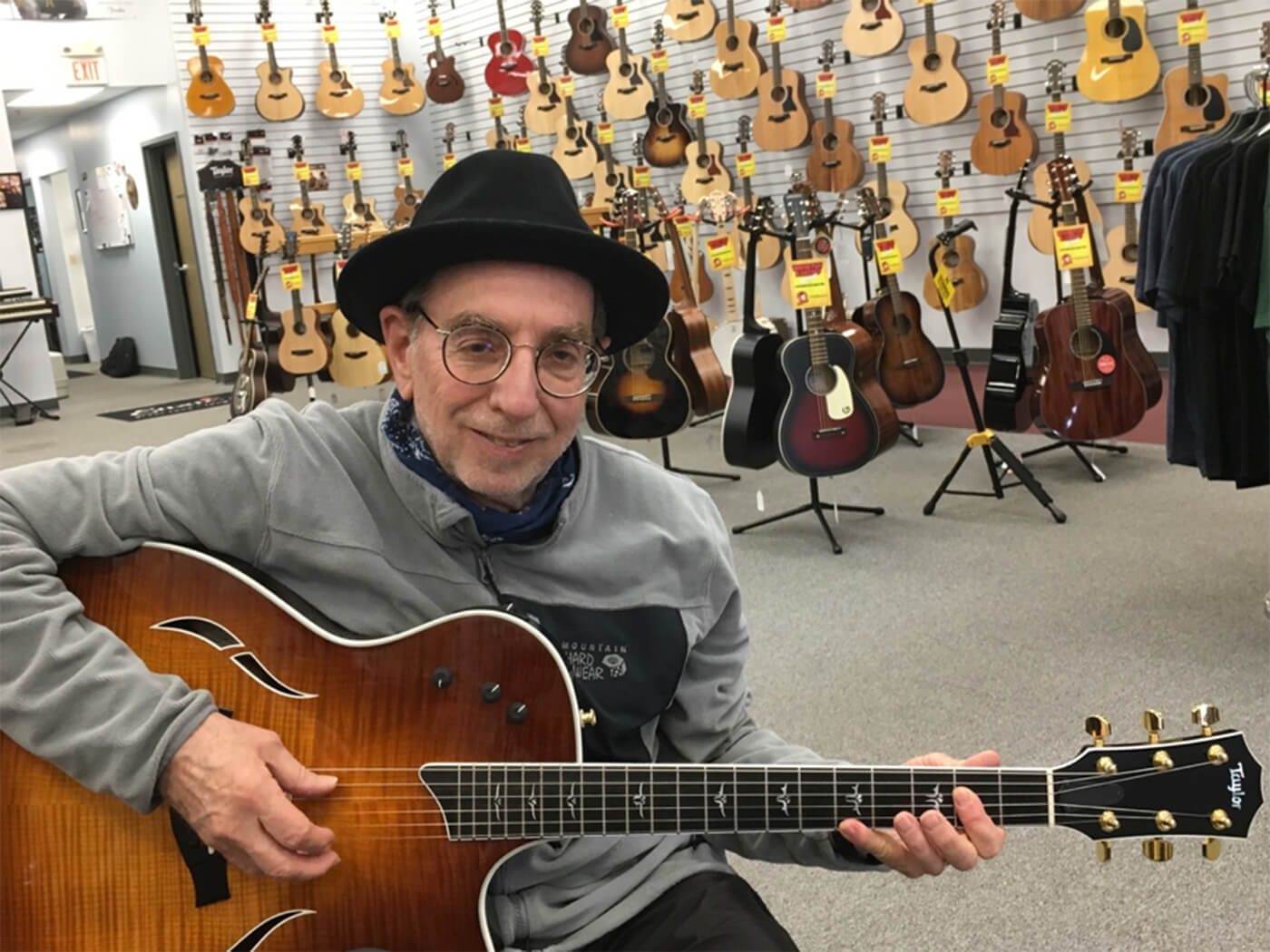 Mitchell Strauss playing guitar in shop