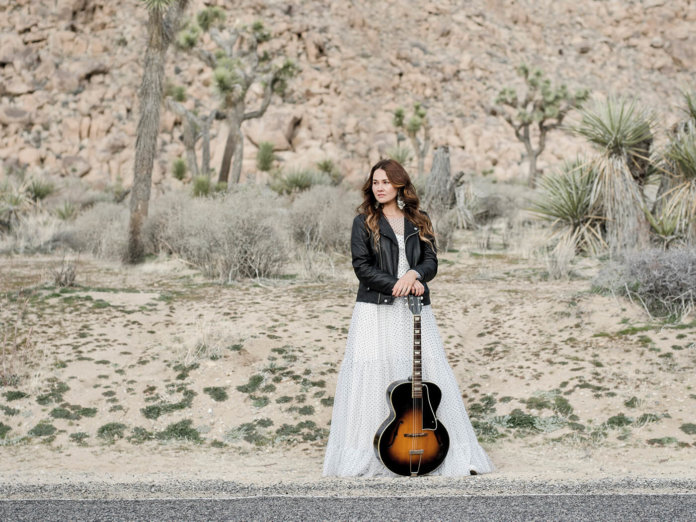 Sinead Burgess standing with guitar near road side