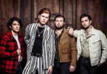 The Amazons press shot against wooden cabinet