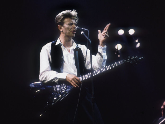 David Bowie on stage with flying v guitar
