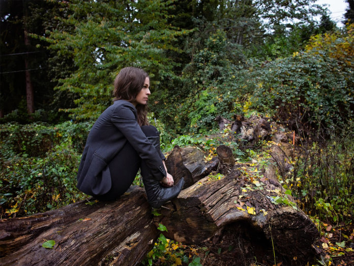 Image of jesca hoop on a fallen tree