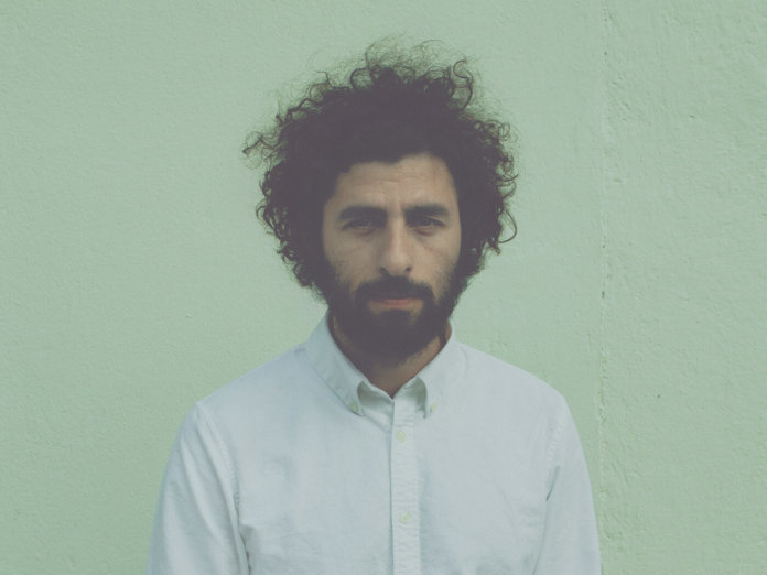 José González press shot against green wall