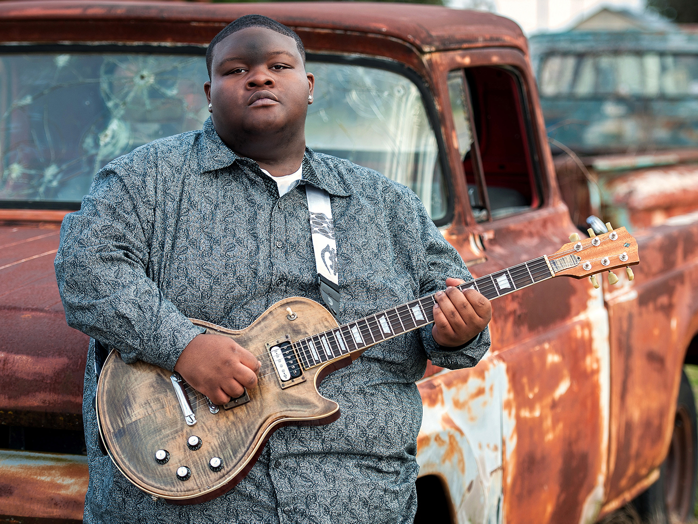 Kingfish posing with guitar in front of truck
