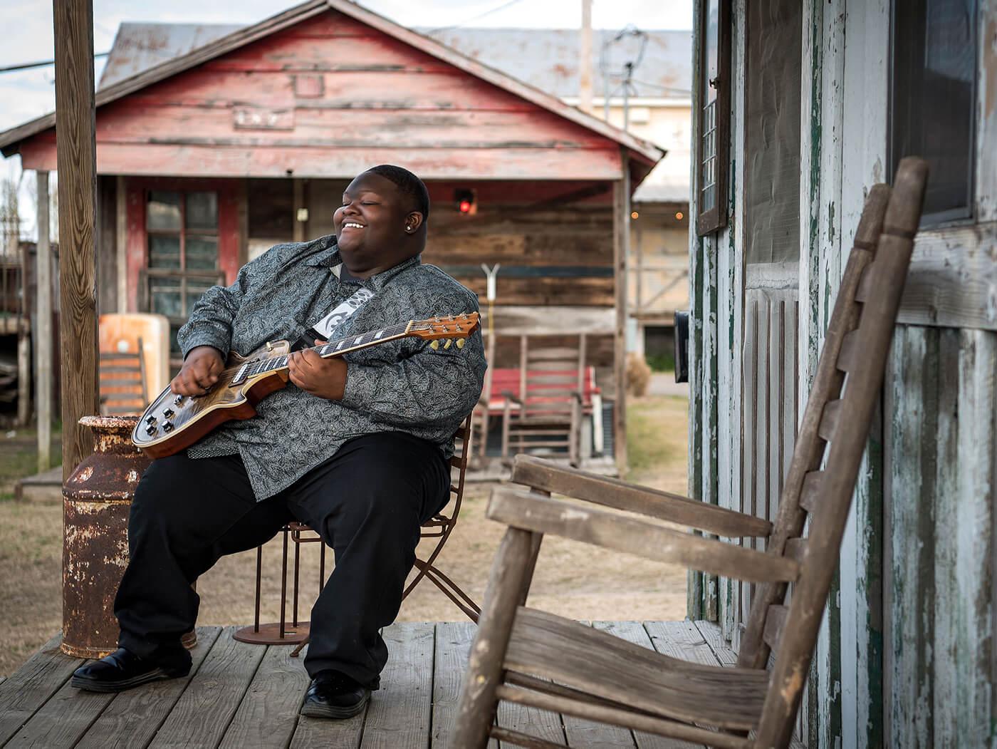 Kingfish sitting outside porch playing guitar