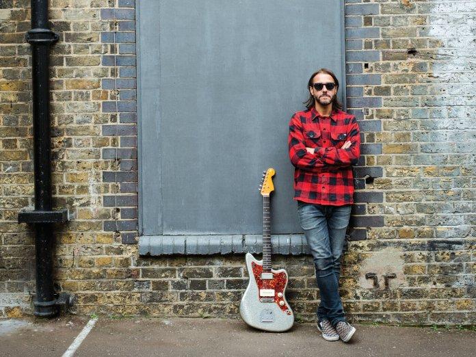 Feeder Grant Nicholas posing with Jazzmaster in front of door