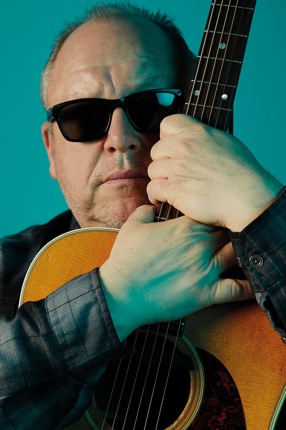 Pixies Black Francis portrait shot holding guitar neck