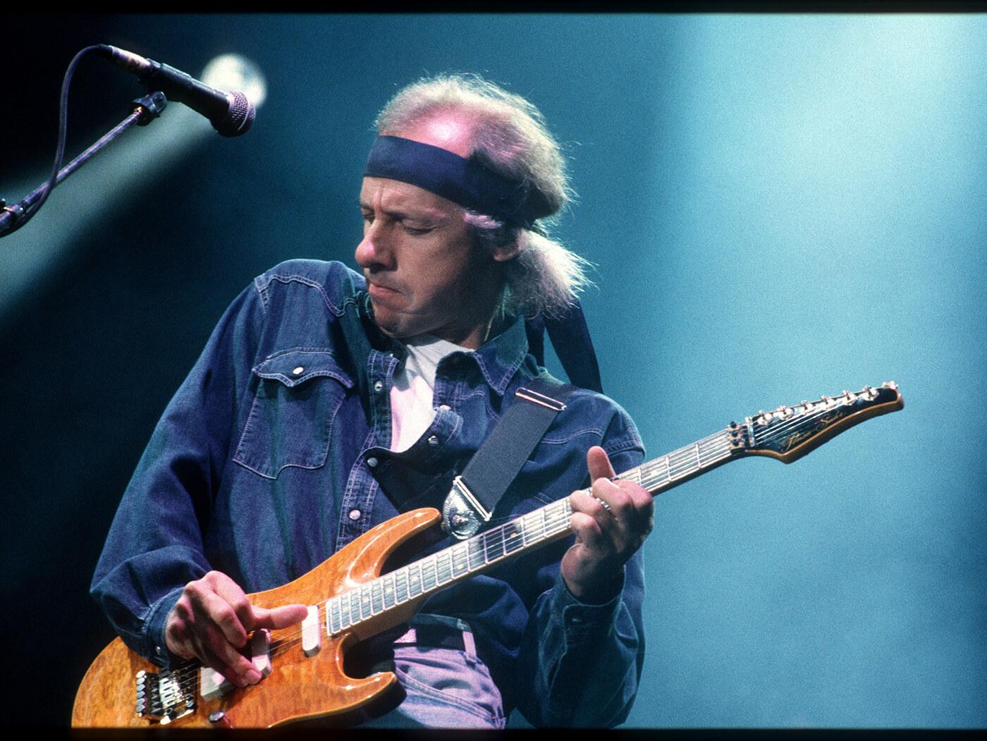 Older Mark Knopfler playing orange guitar