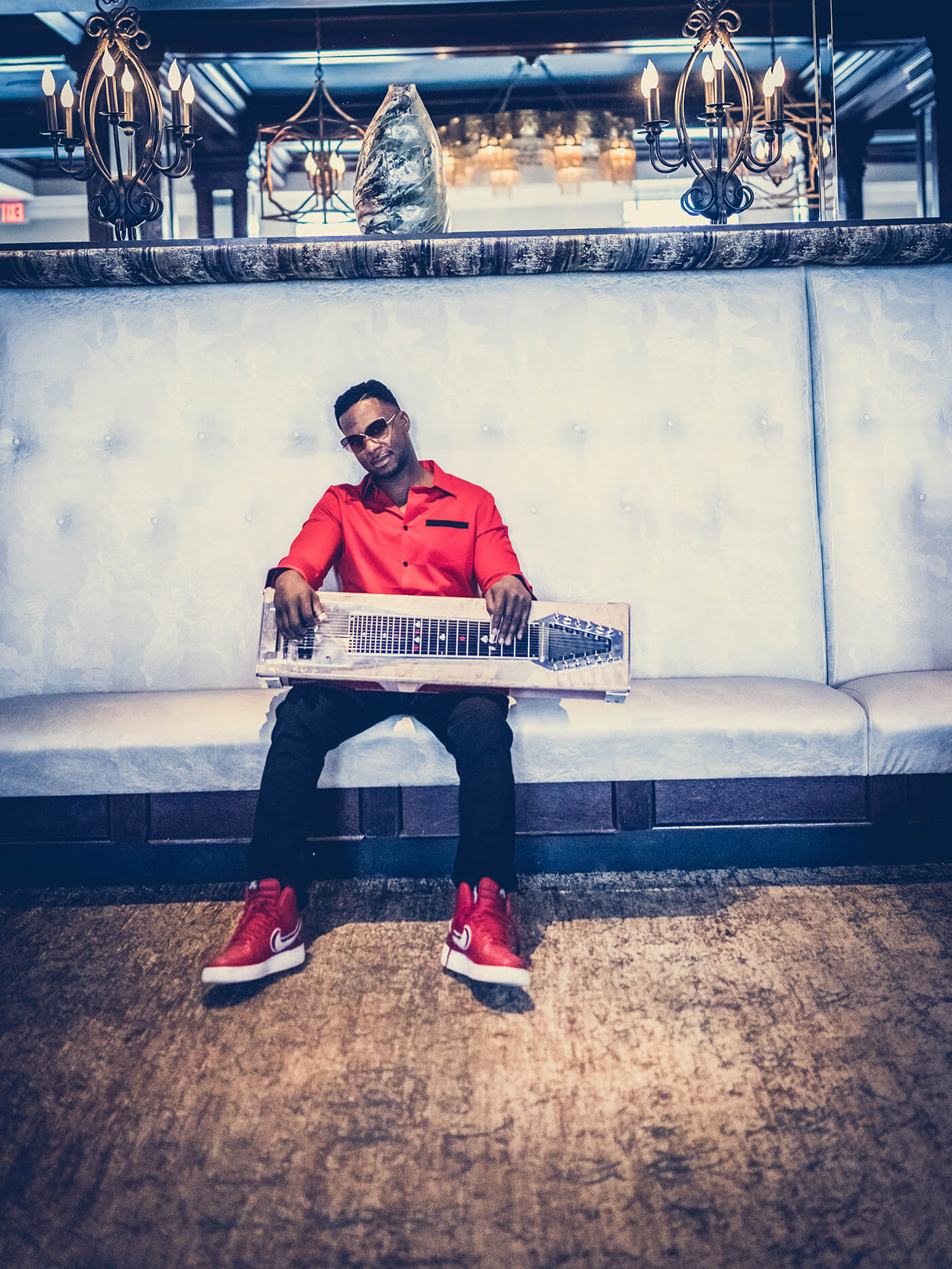 Robert Randolph with lap steel on couch portrait