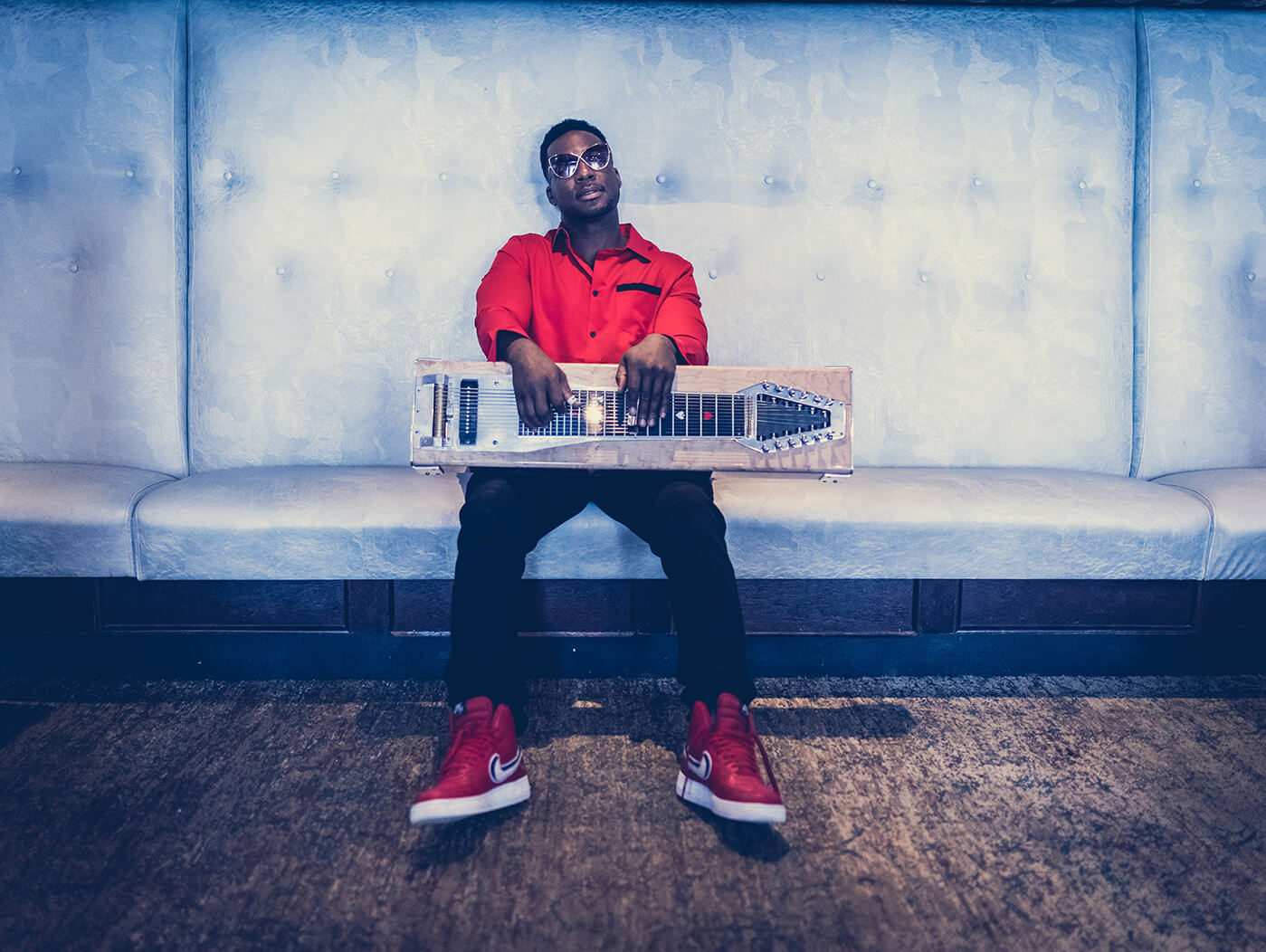 Robert Randolph with lap steel seated on couch