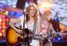Sheryl Crow performing with a Gibson acoustic guitar.