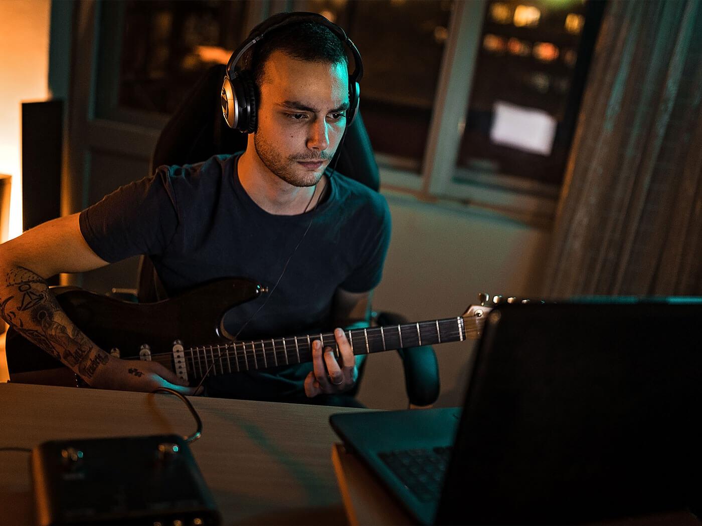 Someone recording guitar in a home studio.
